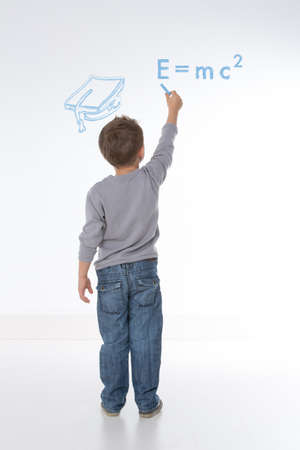 little kid tries to solve equation on the wall Stock Photo