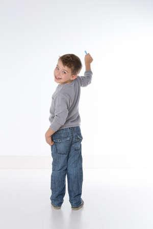 子供の回転背部壁に書いている間 写真素材
