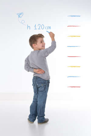 young kid measures his own height on the wall Фото со стока