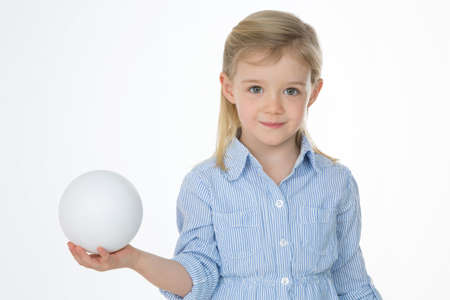 little girl holds perfect sphere in her right hand