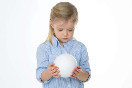 little girl curiously looking at a white ball photo