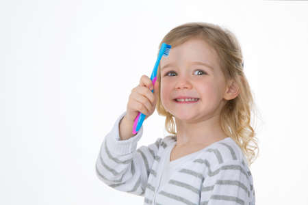 happy child shows her new pink and blue toothbrush photo