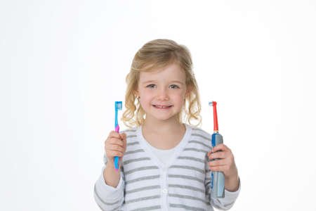curly girl choosing between two different toothbrushes