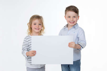 two children showing empty white page Imagens