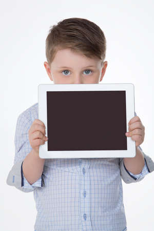 hides: shy male kid hides his mouth behind white tablet