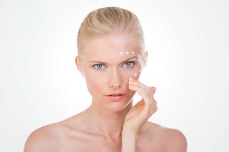 verifying: nordic girl on her face verifying the results of her cream on white background Stock Photo