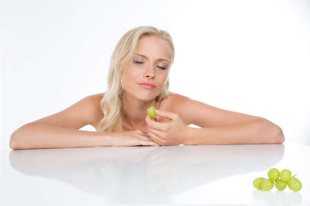 nude blonde woman: sensual pretty girl eats delicious grapes
