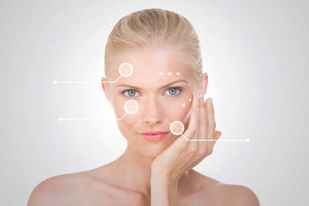 blond girl on grey background with cream on her face Imagens
