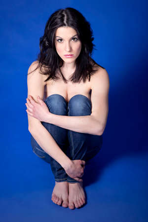 hugging knees: woman with blue jeans sitting hugging her knees