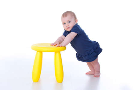 wildcard: Baby standing and leaning on a yellow stool Stock Photo