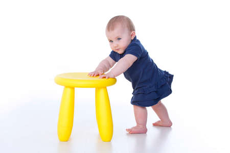 wildcard: baby girl pushes strongly one yellow stool