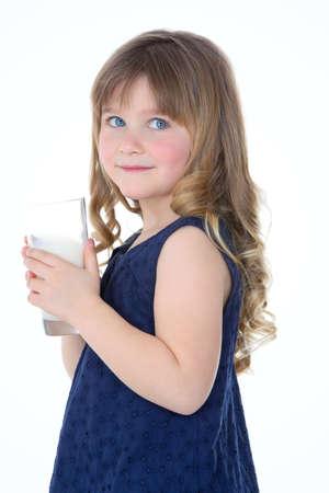 discreto: niña mira a alguien y bebe un poco de leche fresca Foto de archivo