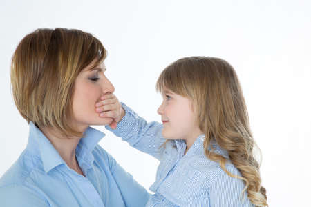 influential: young child covering mouth of her mother with hand Stock Photo