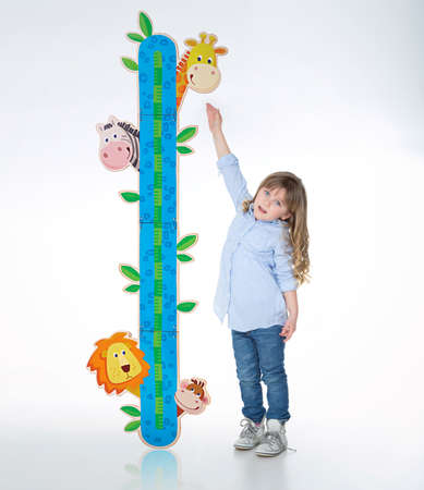 young kid evaluates her height with nice meter Stock Photo