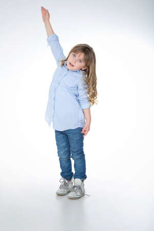 jolie petite fille: petite fille tente d'atteindre le sommet de quelque chose