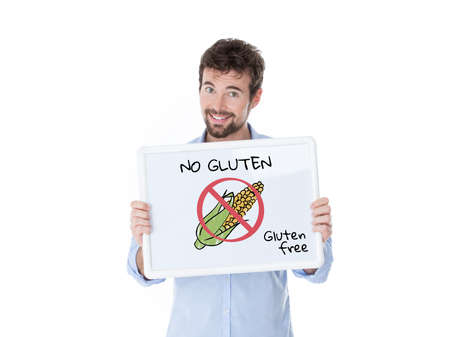 free: smiling guy exhibiting a board with a cob and the message gluten free Stock Photo