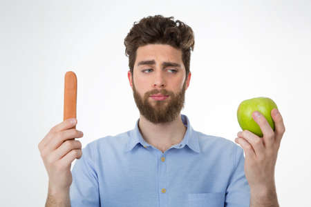 food questions: young cute man thinking about eating a vegan snack or some junk food Stock Photo