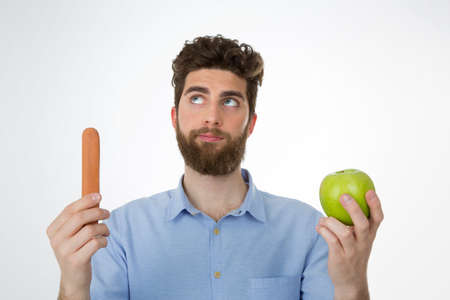unhealthy thoughts: young man with brown hair and beard reflecting about eating an apple or an hot dog