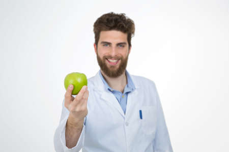 suggests: young doctor with brown hair and beard suggests to eat a healthy apple Stock Photo