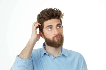 questions and answers: bearded young student standing in front of camera with a doubtfully face