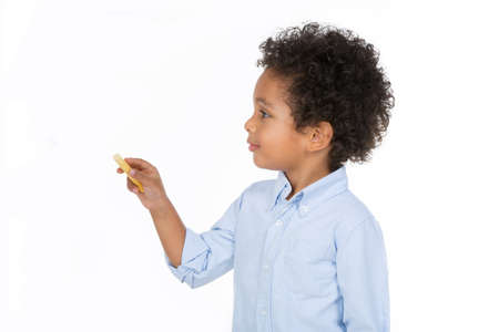 little boy with chalk standing on a white background