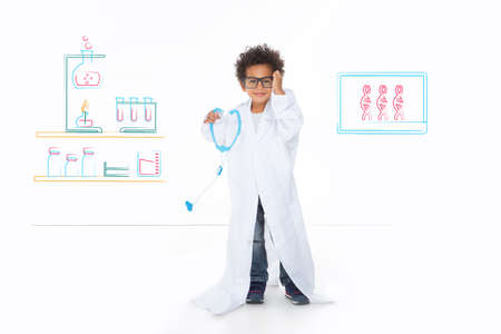 stethoscope boy: little child imagine his future, standing in front of a drawing wall
