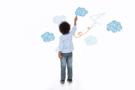 niños escribiendo: niño, pensando en el futuro y la pintura en la pared blanca Foto de archivo