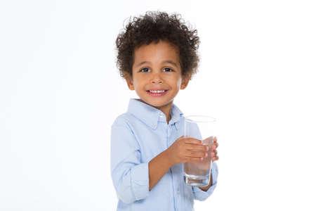 tomando agua: ni�o peque�o con un vaso de agua sonriente aislados sobre fondo blanco