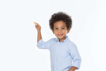 little child looking at the camera holding a yellow chalk Imagens