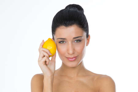girl with yellow lemon looking at the camera