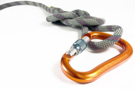 A locking carabiner and a figure eight follow through knot is isolated against a white back ground