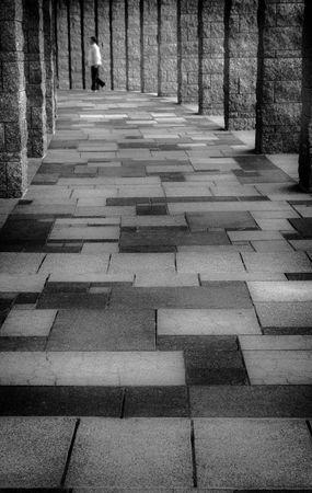 Lone Man Walking in a Hallway