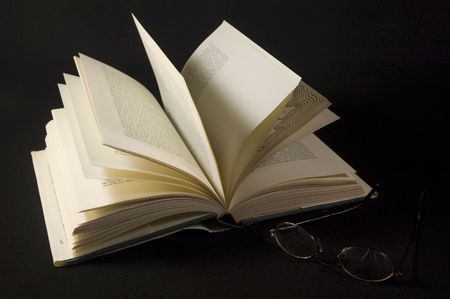 An open book and eye glasses with a black background