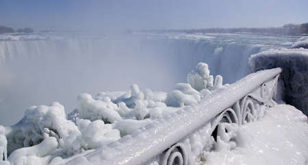 A image of the railing around the niagara gorge covered in ice with the canadian side of Niagara Falls in the background photo