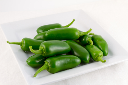 sufficient: A group of freshly picked green Padron chilis on a square white plate with white background