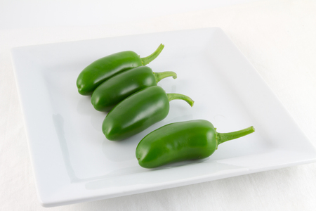 self sufficient: Four freshly picked green Padron chilis on a square white plate with white background Stock Photo