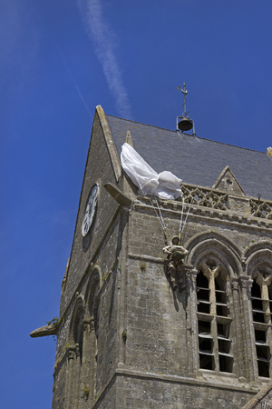 Paratrooper hanging on the roof of the Sainte-Mere-Eglise church in Normandy, France.