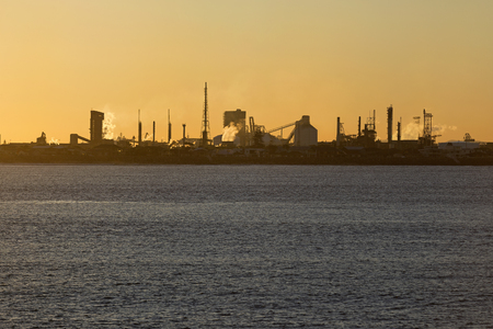 Sunset on the ocean with an industry on the horizon. Newcastle, Australia.