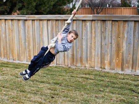 Boy swinging dangerously on rope swing