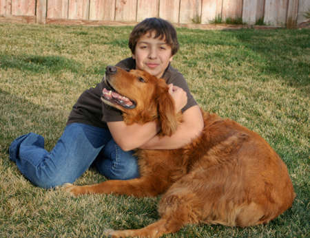 happy teen boy with big red dog