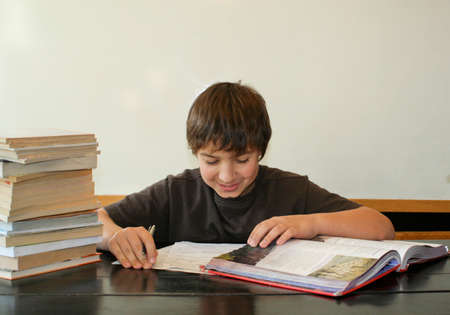 Happy teen boy studying homework with big stack of books  1
