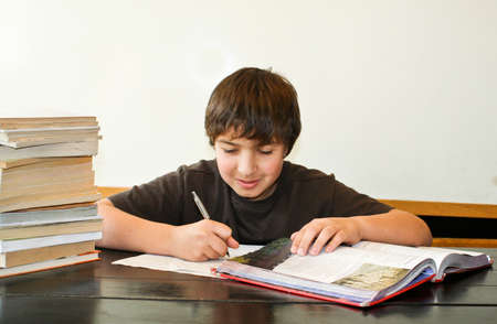 Happy teen boy studying homework with big stack of books  2