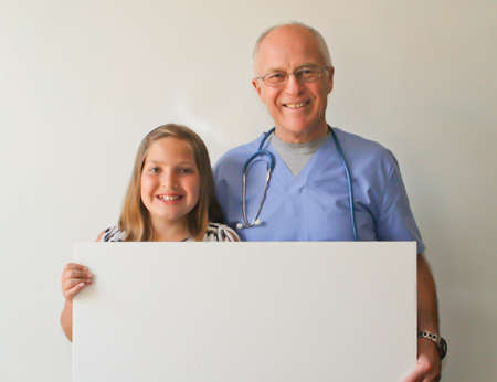 smiling Dr  and young female patient w  blank sign Stock Photo