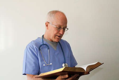 Doctor reading bible Stock Photo