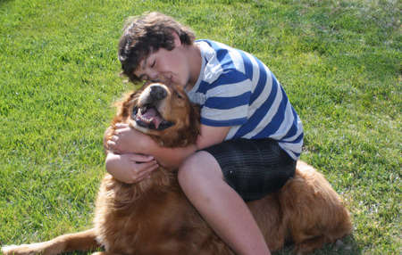 well loved: Teen boy hugging sitting on dog