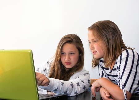 teen girls studying on laptop