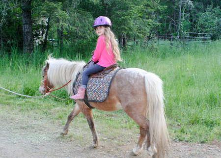 Zeer Jong meisje rijden op pony Stockfoto