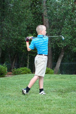 teen golf: Joven golfista masculino adolescente a mediados de swing con forma ejemplar Foto de archivo