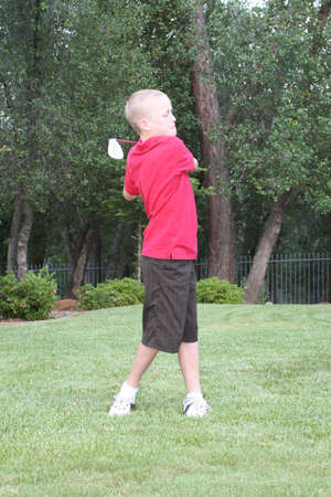 Preteen male golfer  Swinging hard