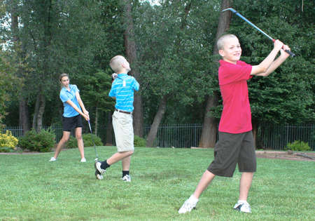 Three young golfers practicing driving skills  Family fun  photo